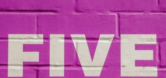 Five spelled in white letters on pink brick wall