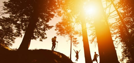 three people hiking one of them jumping up in the air